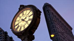 Fifth Avenue Clock with the Flatiron Building at the background in New York City.