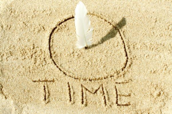 Sundial on the sand with a white feather