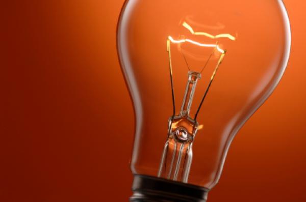 Close up of light bulb against orange background.