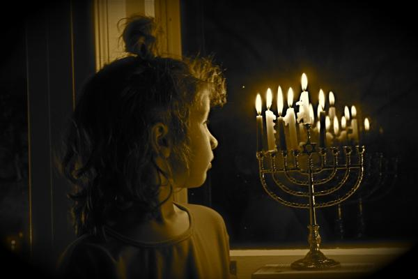 girl on hanukkah looking at Menorah
