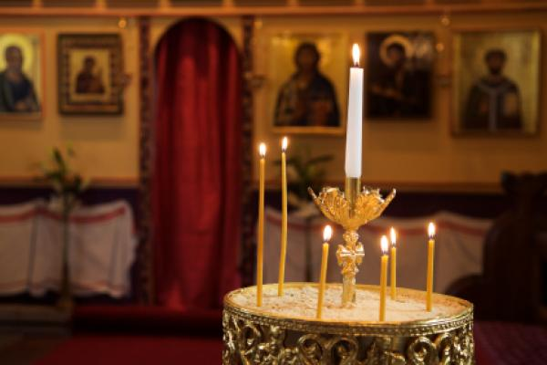 Candle holder and orthodox icons in background