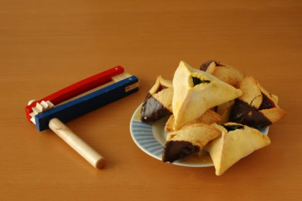 Hamantashen (triangular pastries) and grogger (noisemaker) for the Jewish holiday of purim.