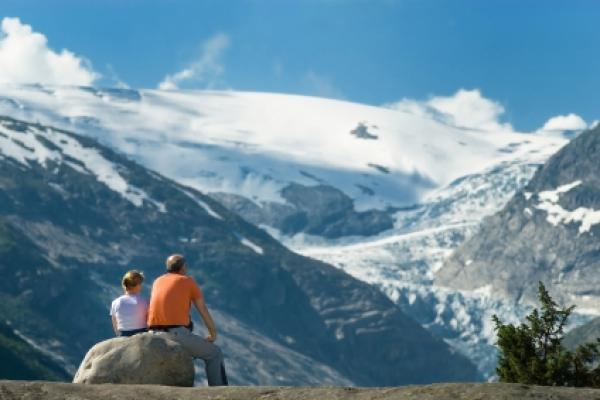 Couple taking a rest and day dreaming on a rock while watching an enormous glacial tongue.
