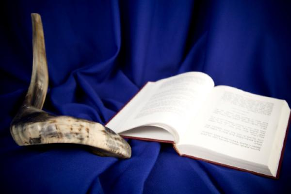 The shofar, an instrument used to blow sound, is pictured with a Jewish holy book.