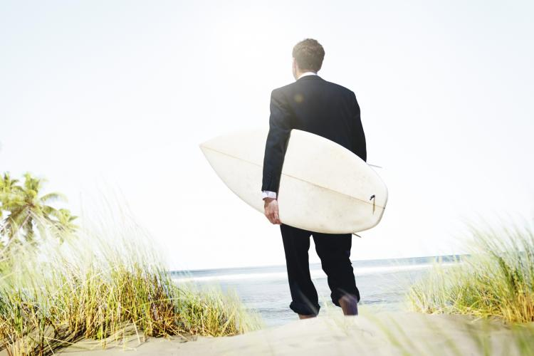 Man in suit with a surfboard on the beach.