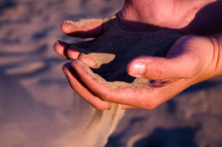 sand running thru hands - symbolizes time running thru your hands
