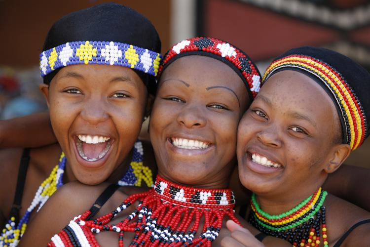 Three young Zulu women friends, dressed in traditional beaded Zulu garments.