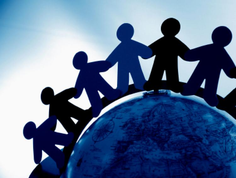 Paper doll people in shades of blue link hands while standing on top of the world
