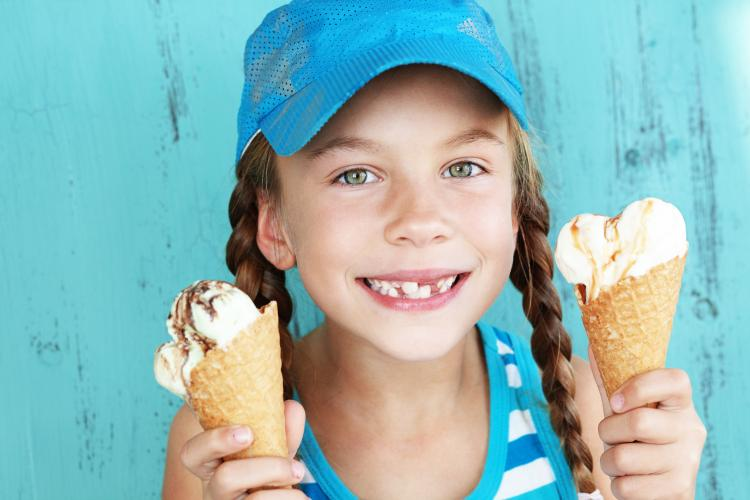 Portrait of 7 year old kid girl eating two ice creams.