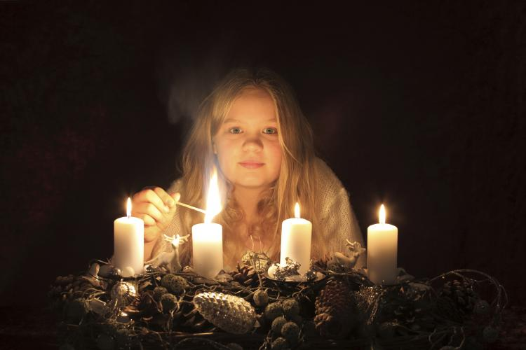 Blonde girl lighting up four Advent wreath candles