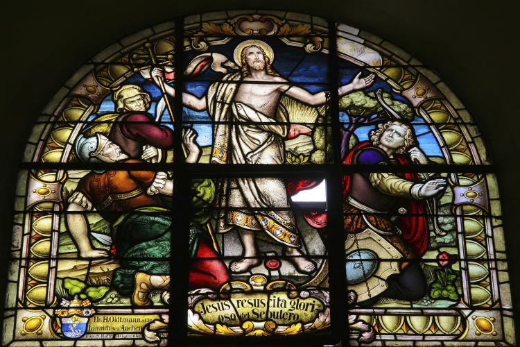 Glass church window depicting the resurrection of Jesus Christ on Easter morning.