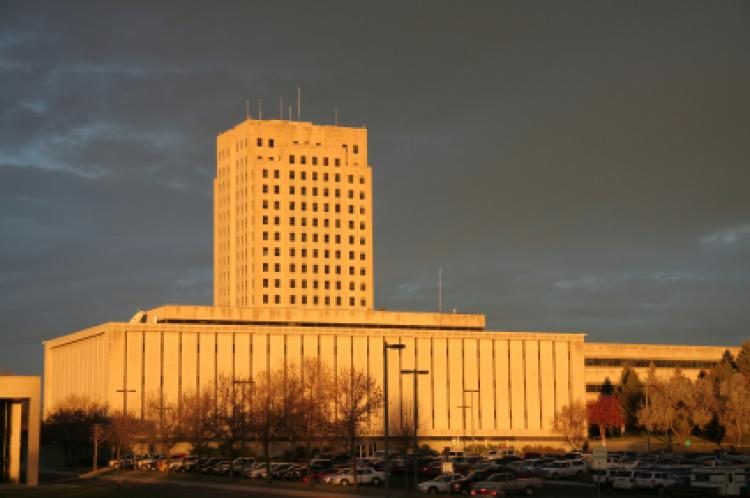North Dakota capital tower with Department of Transportation building in foreground in early morning light.