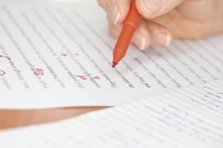 Hand with red pen proofreading a story.