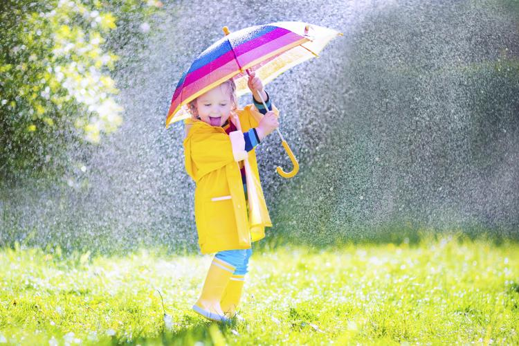 Laughing toddler with umbrella playing in the rain.