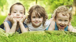 Three young children lying in the grass smiling.