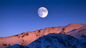Moon rising over snowy mountains.