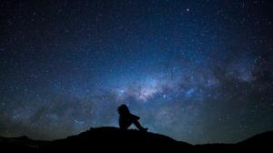 A man's silhouette with the milky way and a meteor in the backdrop.