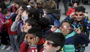 Children watching a solar eclipse wearing protective tinted glasses.