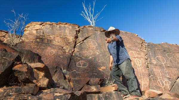 Aboriginal man at Chambers Gorge aboriginal engraving site in Flinders Ranges, South Australia.