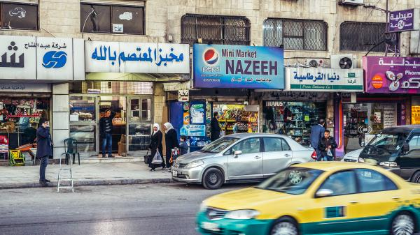 Busy street with shop fronts and taxi in Amman, Jordan.