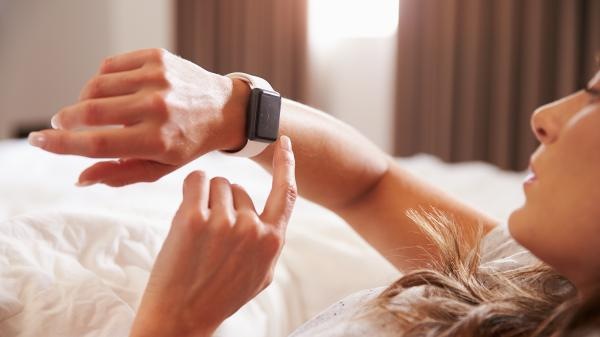 Woman looking at her watch after waking up.