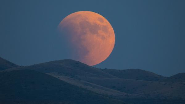 A partially red Moon rising from behind mountains.