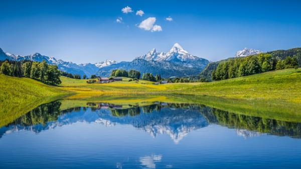 Bright blue sky and landscape reflecting in a lake in the Alps.