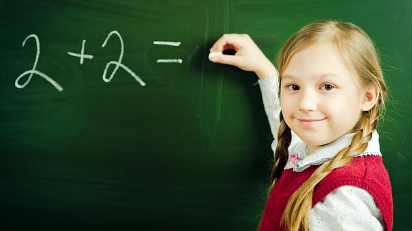 a young girl doing a simple calculation on a blackboard smiling at the fotographer.