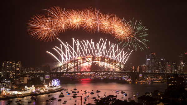 Fireworks at night over a bridge. Boats on the river under the bridge.