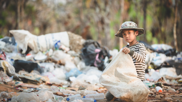 Small boy kneeling on a waste dump holding a large sack and collecting garbage.