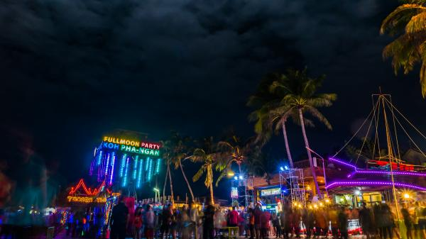 Partygoers on the beach at night amongst neon lights in Haad Rin, Ko Pha Ngan, Thailand.
