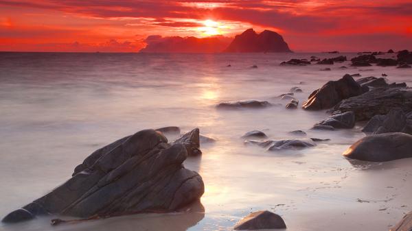 Midnight sun by the sea on island of Vaeroy, Norway.