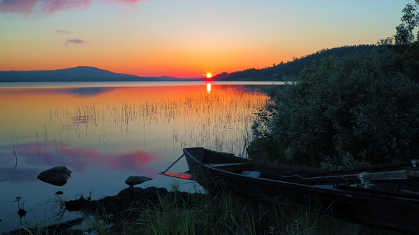 Image of the midnight Sun above a lake in the province of Norrbotten, Sweden.