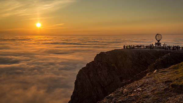 Photo of people on a cliff looking at the midnight Sun in Nordkapp, Norway.