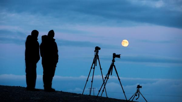 Silhouette of two photographers looking at the Full Moon.