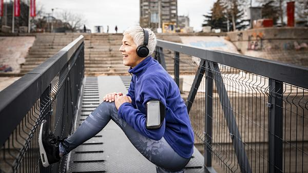 Grey haired senior woman in sports clothing stretching on a bridge and listening to music.