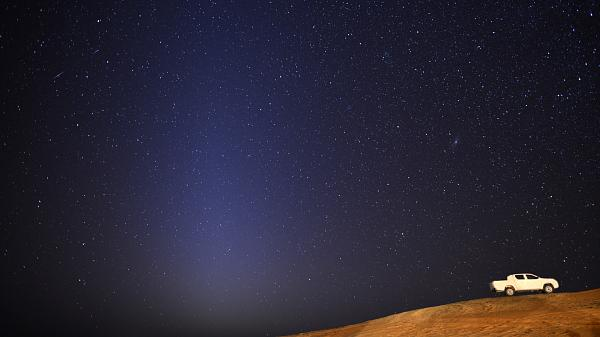 Starry night sky in the background with desert in the foreground. White truck on the side and a triangular glow of zodiacal lights in the sky.