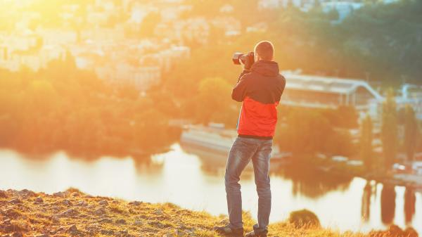 A photographer taking pictures at sunset.