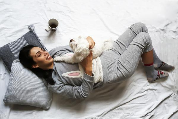 Woman relaxing on a bed cuddling a white dog with cup of coffee next to her.