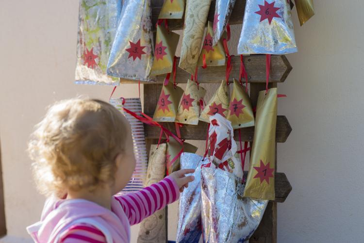 Little girl reaching for a gift in a home made advent calendar on the wall.