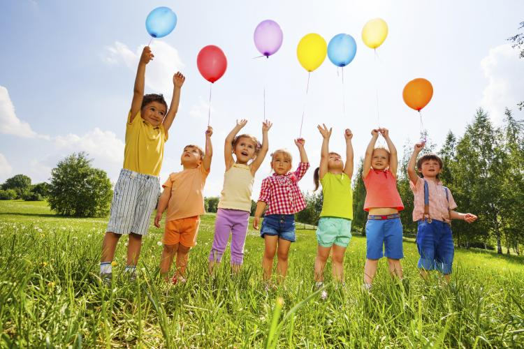 Happy kids with balloons and arms up in the sky.