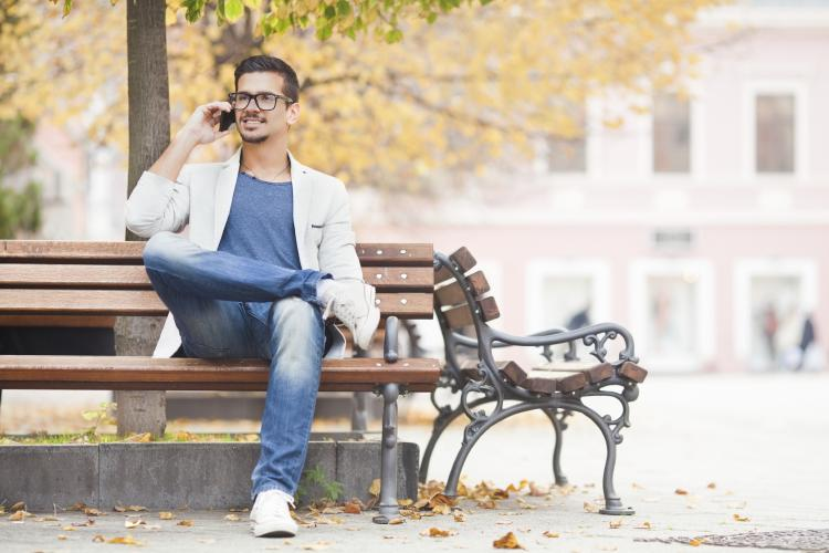 Relaxed man on park bench on the phone.