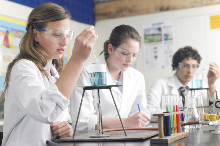 Students in a lab using a bunsen burner.