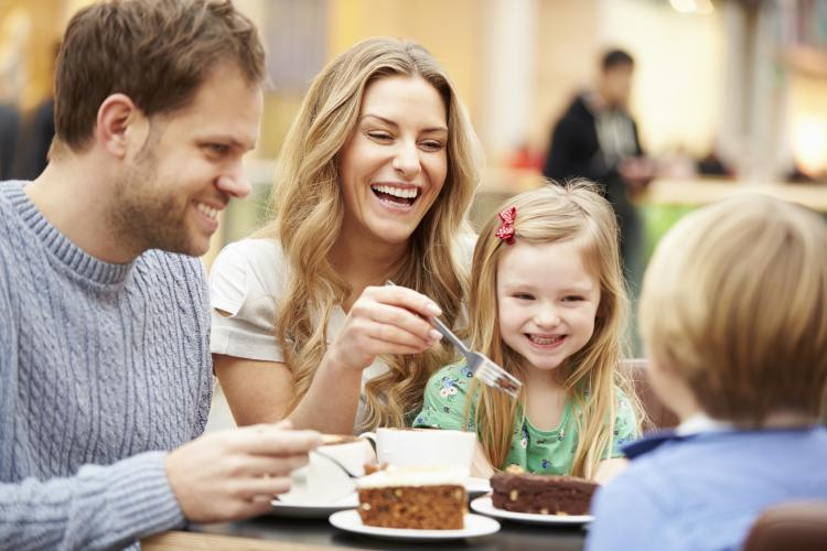 Family enjoying cake in café together.