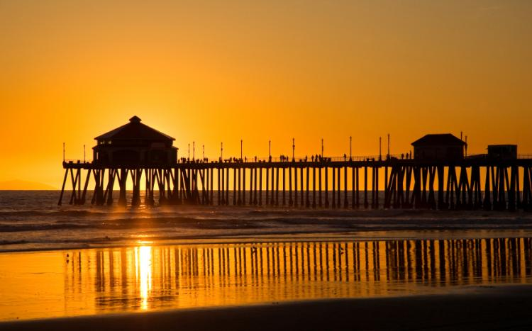 Pier silhouetted against the sunset on a California beach.
