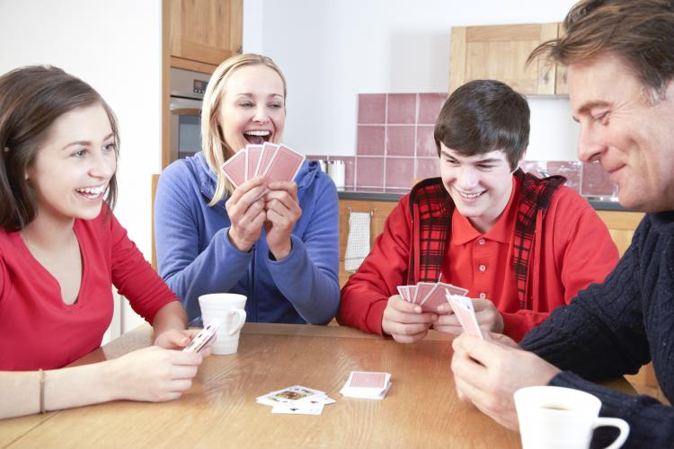 Family playing cards in kitchen.