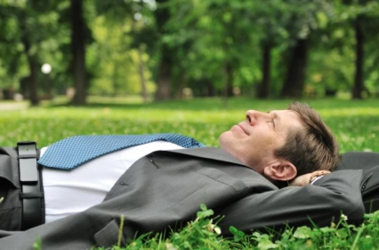 Man dressed in a suit lying down relaxing on a lawn with his head resting on his arms.