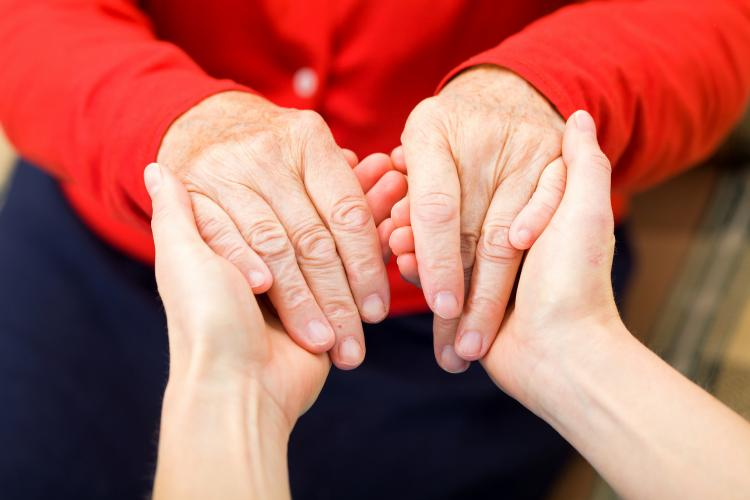 Young woman holding hands with elderly woman.