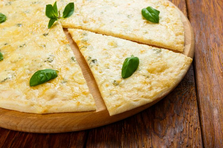 Four cheese pizza with basil leaves.