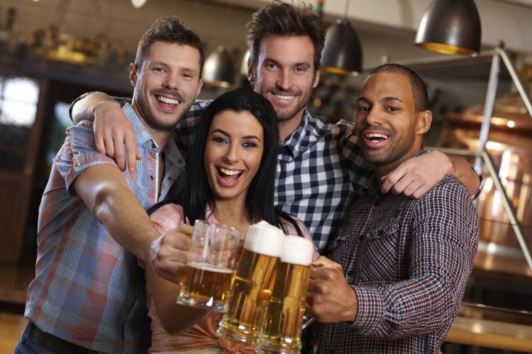 Group of happy friends clinking with beer in pub.